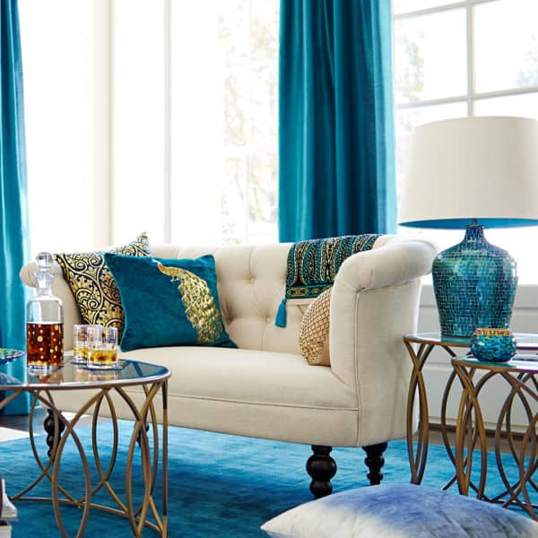 combine peacock blue curtains and rug with gold accents for an expensive-looking living room