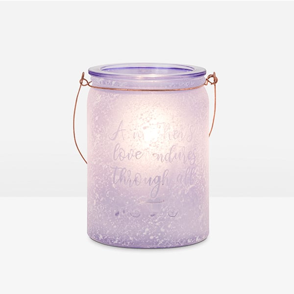 """Celebrate the enduring glow of motherly love with this heartfelt warmer. Its message reads: """"A mother's love endures through all."""""""