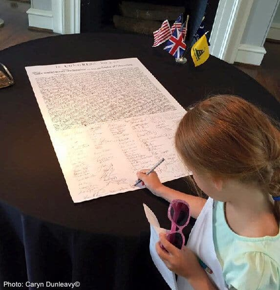 A girl signs the declaration of independence