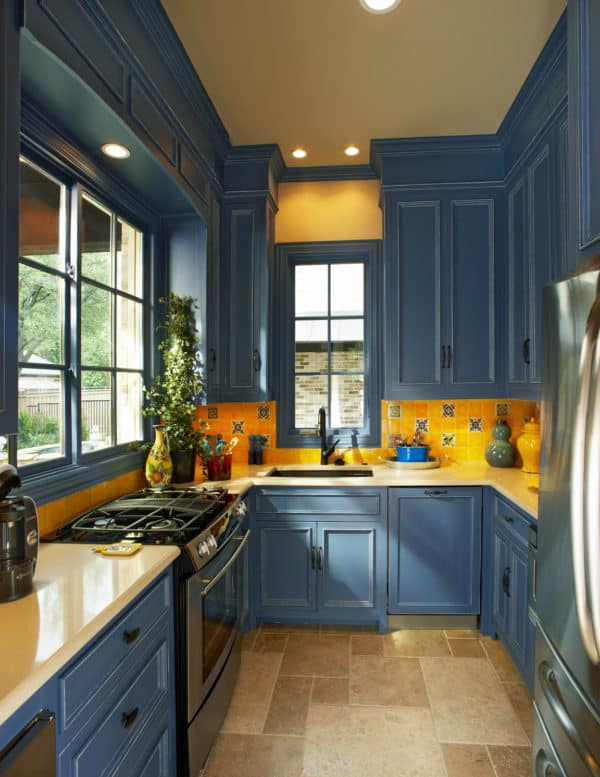 classic u-shaped kitchen with prussian blue cabinets and fire yellow ceramic backsplash
