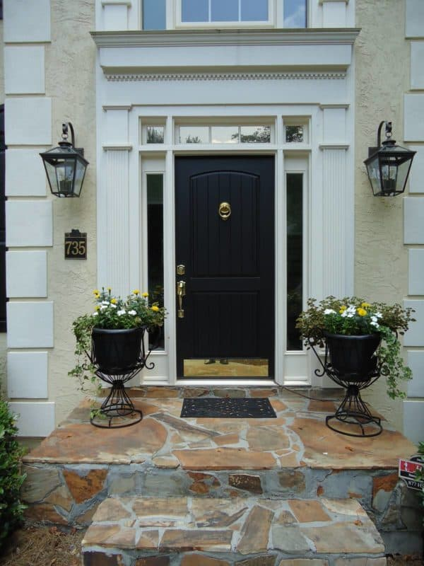 try a black front door color for a bold and timeless tan exterior