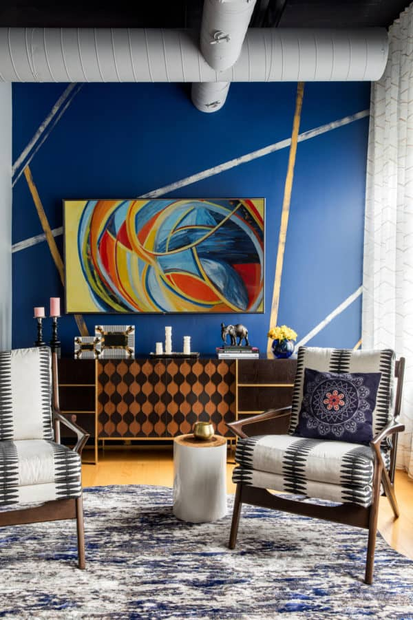 an artistic living room featuring blue accent wall and gold velvet upholstered chairs