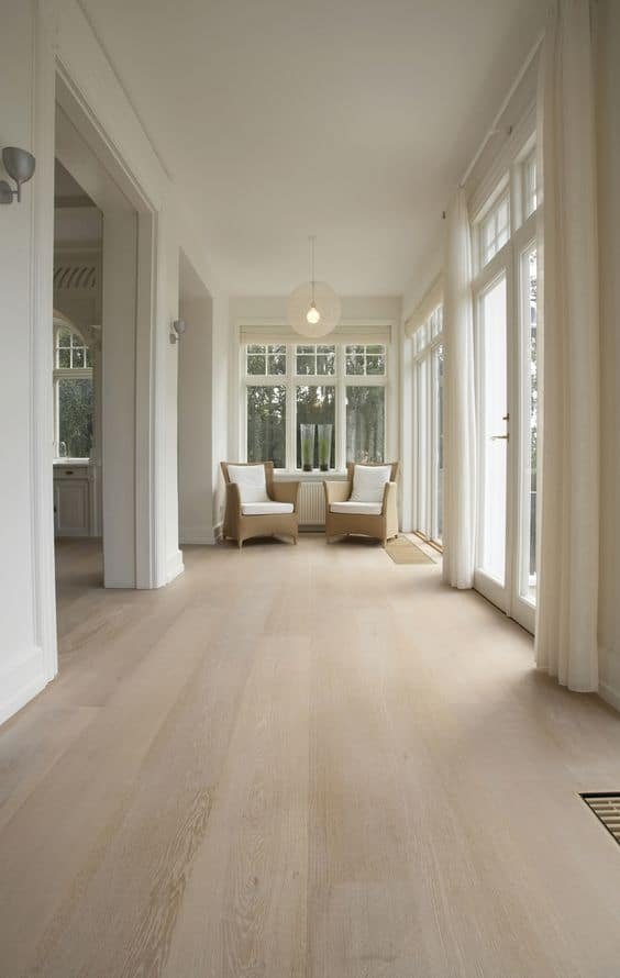 light coloured vinyl tiles for floor with off-white curtains, white walls, and neutral shade sofas.