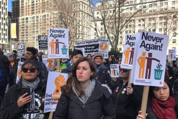 """Protestors holding signs that say """"Never Again!"""""""