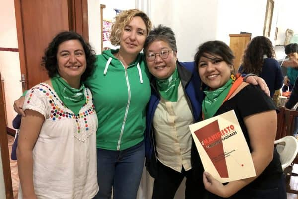 Four women pose with a copy of The Radical Women Manifesto.