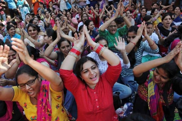 A large crowd of women in brightly colored saris clap their hands over their heads in unison.