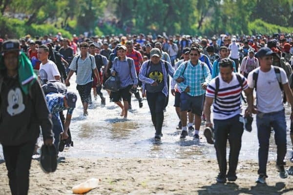 Dozens of men, many carrying their shoes, run across a shallow part of a river.
