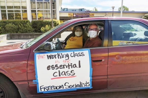 "A car protest: two people in facemasks look out the window of a car. The side on the side reads ""the working class is the essential class."""