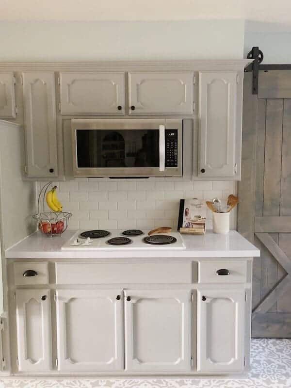 painted kitchen cabinets with stovetop and microwave