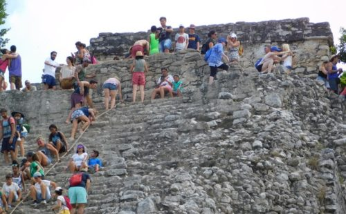 Tourists climb the ruined pyramid at coba