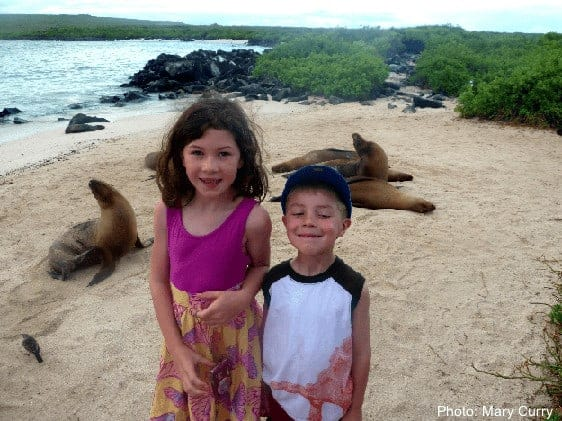 Kids mugging in front ot eals on a galapagos beach