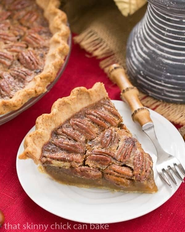 Classic Pecan Pie, with a boozy twist on a white dessert plate with a bamboo handled fork