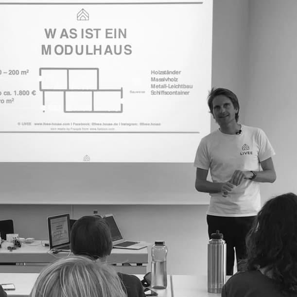 Das Bild zeigt den Tiny House Experten Christian Brecht bei einem Vortrag. Zu sehen ist der Referent und eine Powerpoint Präsentation über Tiny Houses