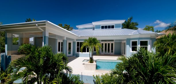 a beach-style exterior with light blue stucco and white trim