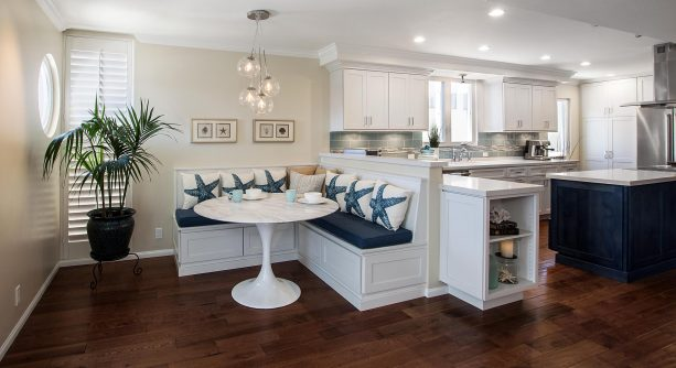 a half wall connected to a custom L-shaped banquette in a beach-style open kitchen and dining room