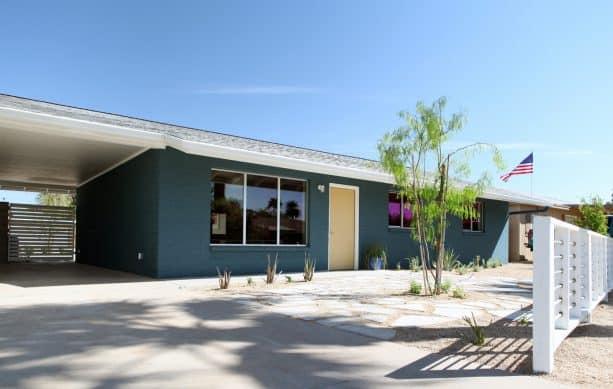 a modern ranch house with greenish-blue brick walls