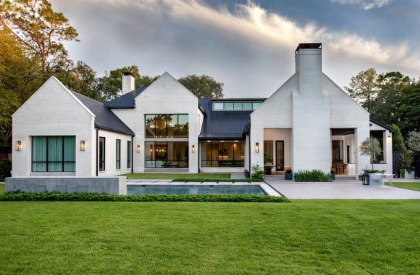 a transitional white brick house with black metal roof