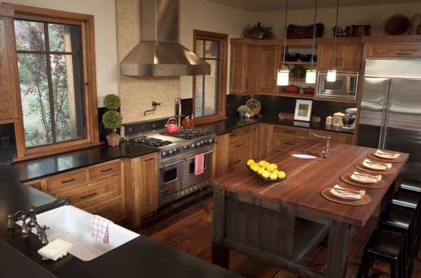 hickory cabinets, dark wood floor, black countertops, and black backsplash in an elegant kitchen