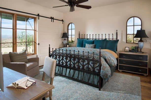 a black metal bed with gorgeous design and teal pillows in a Mediteranean-style bedroom