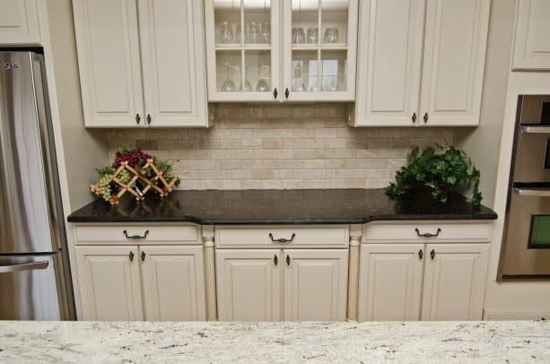 antique white cabinets with dark granite countertops
