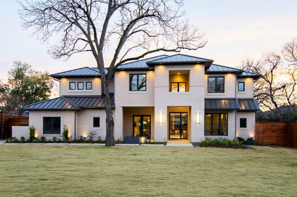 a transitional cream brick house exterior with charcoal metal roof