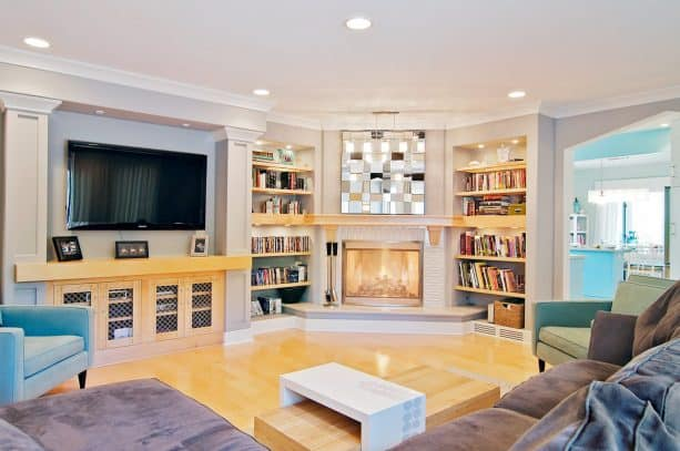 a fireplace and a pair of bookshelves uniquely located in the corner of a contemporary family room