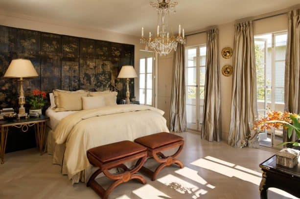 a traditional bedroom with black and gold accent wall and gold curtains