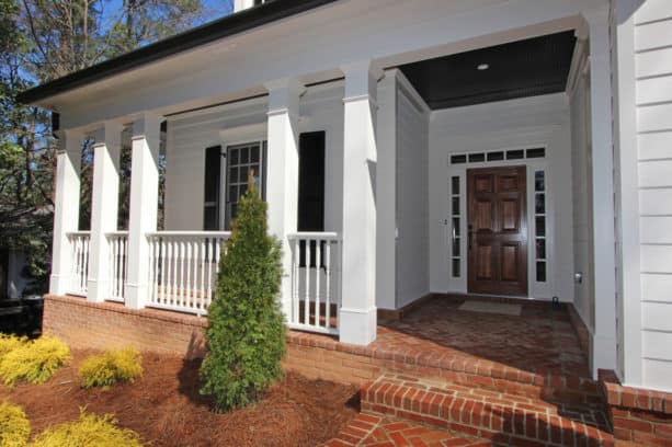 a white wall siding paired with red brick floor in a traditional exterior