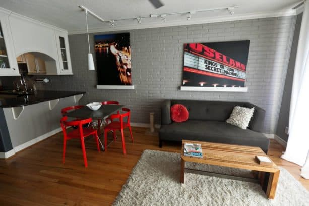 textured grey brick walls and red details in a modern dining-living room