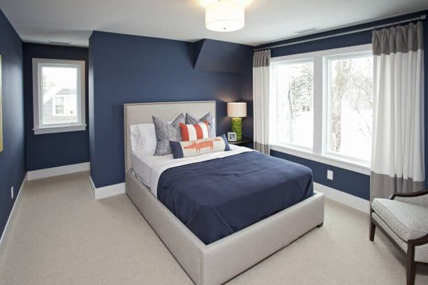 a navy blue bedroom with grey bed