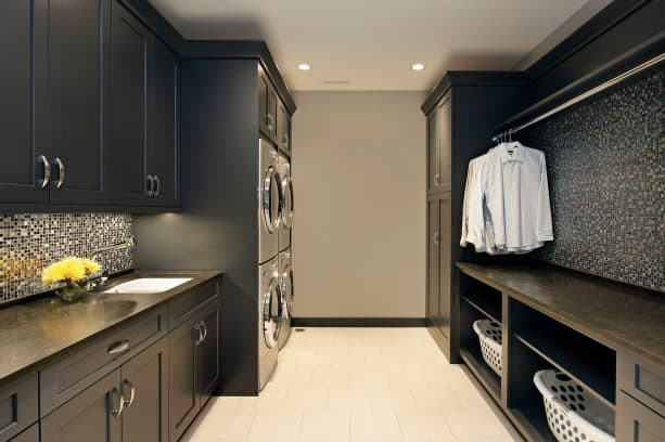 laundry room with black cabinets and beige walls