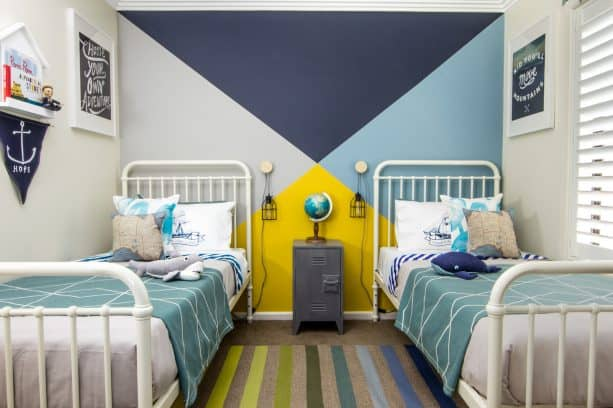 a shared bedroom with 4-tone, including navy, accent wall