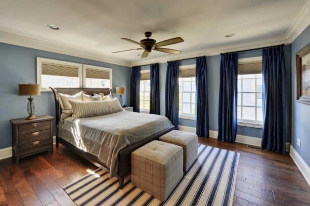 a traditional bedroom with blue walls and navy blue curtains