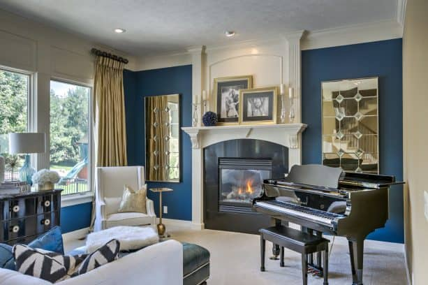 a transitional living room with dark blue walls and gold curtains
