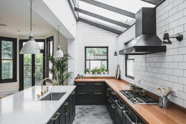 white subway tile wall and dark gray grout in an industrial open kitchen design