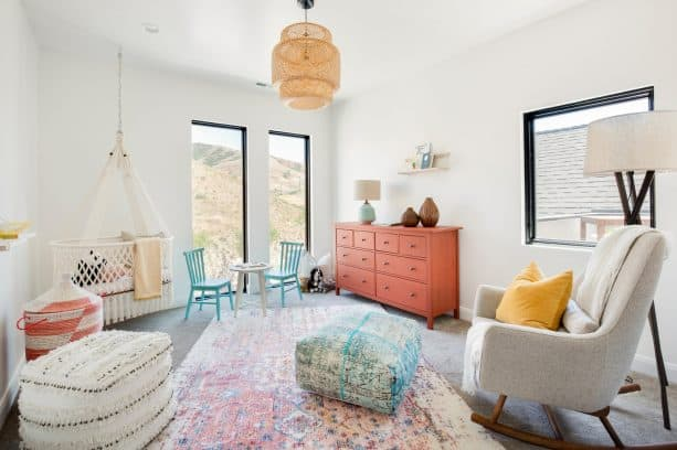 turquoise chairs and coral drawers in a transitional nursery room