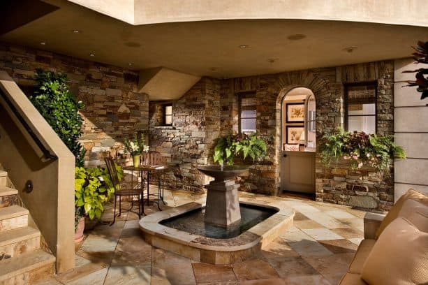 a contemporary walkout basement patio with fountain feature