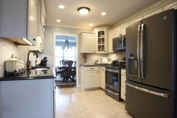 a traditional kitchen with white cabinets and black slate appliances