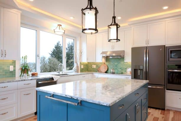 a transitional kitchen with white cabinets, slate appliances, and blue island