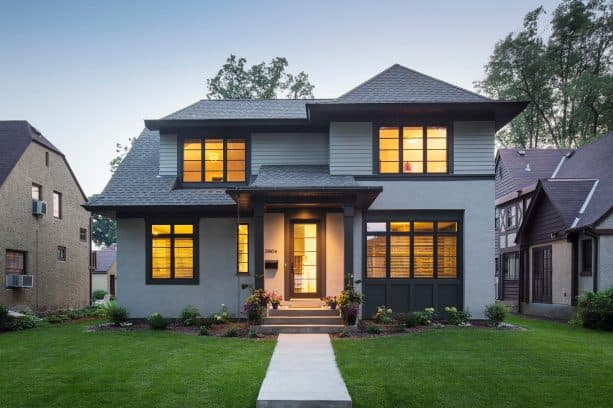 a bold traditional exterior with black trim and grey stucco