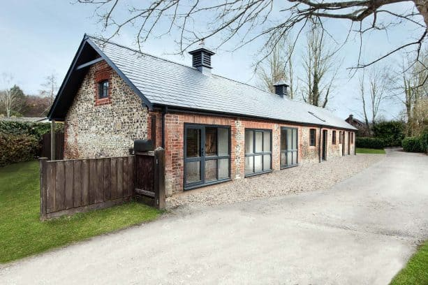 a rustic stable house with red brick wall and metal roof shingles