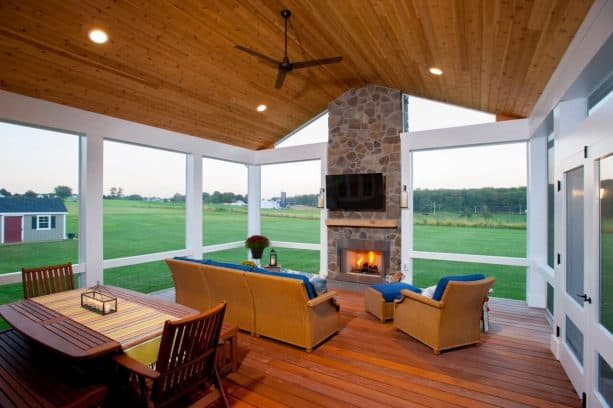 a stone fireplace in a simple, rustic screened porch