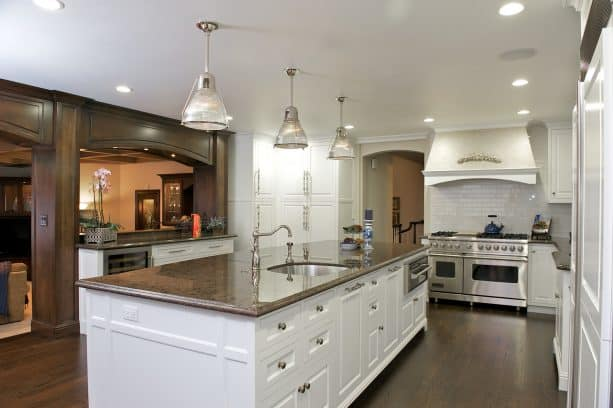 a kitchen looks clean because of the clean white cabinets, silver colors, and brown granite combo