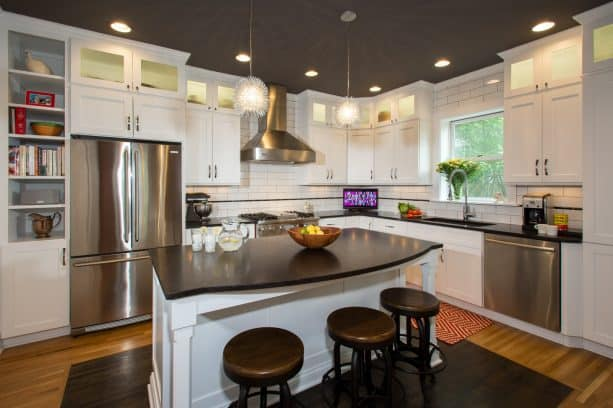 a traditional kitchen with stainless-steel appliances, white cabinets, and leathered-finish brown granite countertops