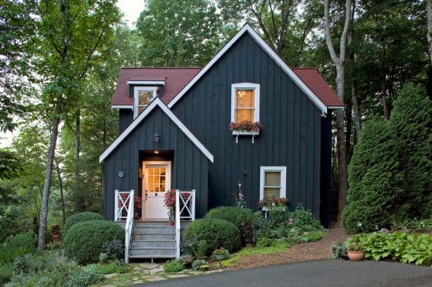 a fabulous traditional mountain home with black -painted vertical siding