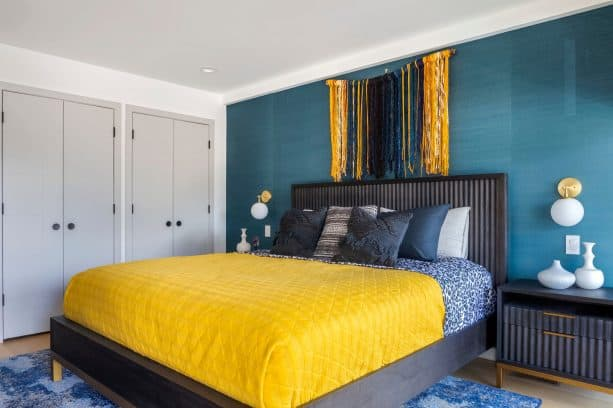a contemporary black and teal bedroom with fun touches of yellow