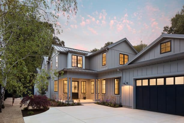a welcoming two-story cottage in farmhouse style with Summit Grey SW 7669 paint on the board and batten exterior