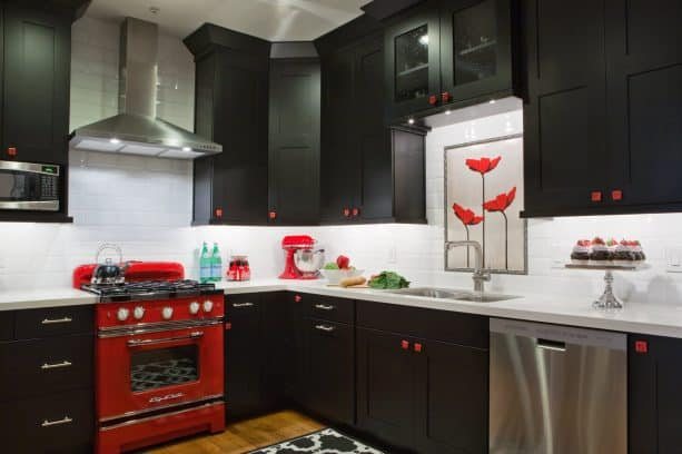 bold eclectic kitchen with dominant black cabinets that are paired with white subway tile backsplash and stunning red oven stove