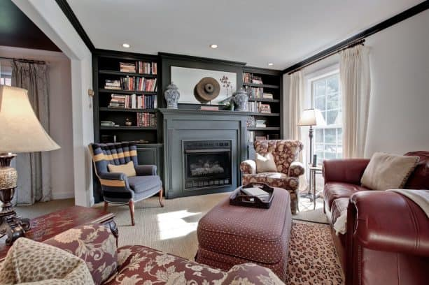 grey fireplace with black bookshelves in a traditional living room with reddish brown furniture pieces