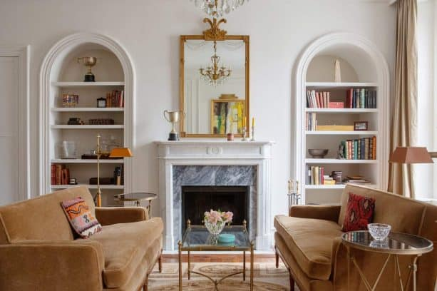 wall-built-in bookshelves flanking a gorgeous fireplace with marble filler panel
